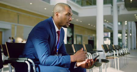 etnia africano : Side view of African american Businessman practicing speech in the lobby at office. He is using mobile phone 4k