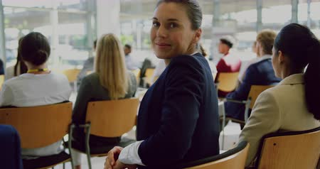 przedsiębiorczość : Side view of Caucasian Businesswoman looking at camera during seminar. She is smiling 4k Wideo