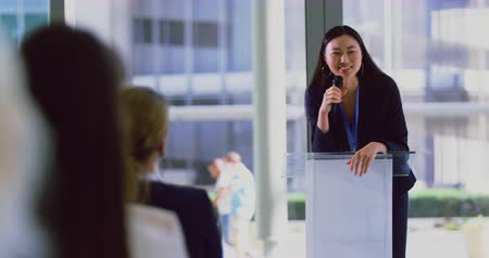 podyum : Front view of asian female speaker speaks in a business seminar at modern office. Business people waving American flag 4k