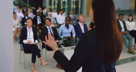 length : Rear view of Asian female speaker speaks in a business seminar. Business people listening to her 4k