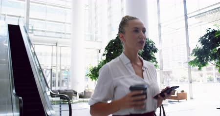 sofisticado : Side view of Caucasian Businesswoman using mobile phone and walking in the lobby at office. She is drinking coffee 4k
