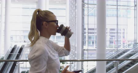 kifinomult : Side view of Caucasian Businesswoman using mobile phone and drinking coffee in the lobby at office. She is walking 4k