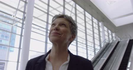 kifinomult : Front view of Caucasian Businesswoman looking upwards in the lobby at office. She is smiling and looking at camera 4k