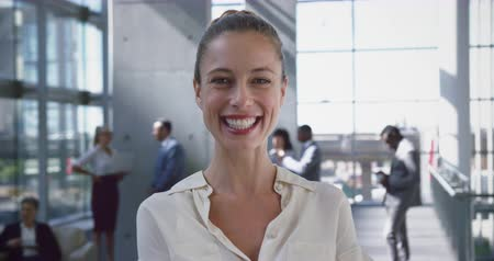 sofistike : Front view of Caucasian Businesswoman looking at camera in the lobby at office. She is smiling 4k Stok Video