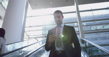 lobby : Low angle view of Caucasian Businessman using mobile phone on escalator in a modern office. He is smiling 4k