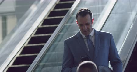 teljes hosszúságú : Front view of Caucasian Businessman using mobile phone on escalator in a modern office 4k Stock mozgókép