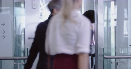 коридор : Rear view of African american Business people getting in the elevator at modern office. They are interacting with each other 4k Стоковые видеозаписи
