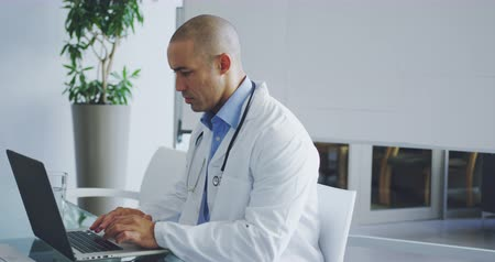 病院 : Slow motion panning shot of young mixed race male doctor sitting at desk in office using laptop, side view. 4k 動画素材