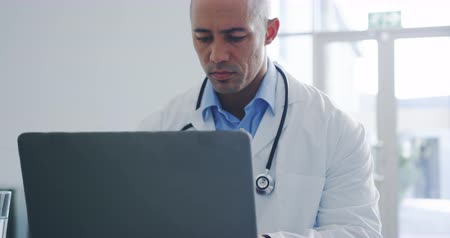 oturma : Close up front view tilt shot of young mixed race male doctor sitting at desk in office using laptop. Slow motion. 4k