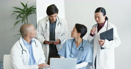 クリップボード : Handheld front view of multi-ethnic group of four young doctors working together at desk using laptop and tablet, one holding clipboard 4k 動画素材