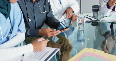 internar : Mid-section close up of doctors sitting at a table in a meeting looking at x-ray on a tablet computer 4k Stock Footage