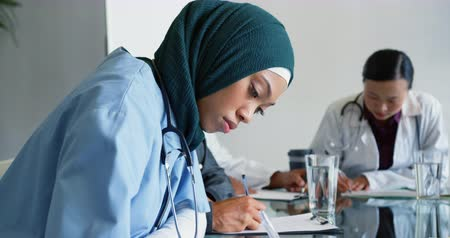 сосредоточиться на переднем плане : Handheld close up shot of young mixed race female doctor wearing hijab sitting at table writing. She stops, turns to camera and smiles. Two other young doctirs are sitting at table working in the background. Focus on foreground. 4k