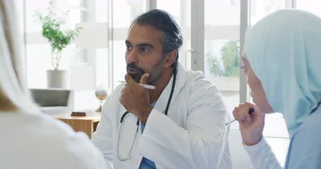 estagiário : Close up handheld shot of middle aged mixed race male doctor sitting at a meeting talking with colleagues. The mixed race young woman on the right is wearing a hajib 4k