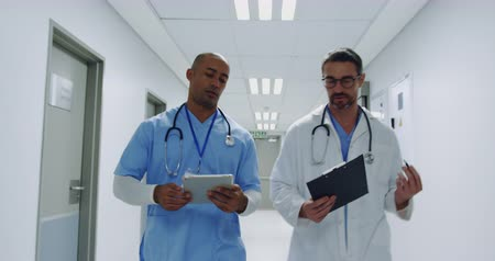 internar : Waist up reverse tracking shot of a mixed race and Caucasian male doctor discussing notes in a hospital corridor 4k