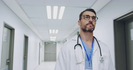 lekarstwa : Low angle waist up reverse tracking shot of middle aged Caucasian male doctor walking in a hospital corridor 4k Wideo