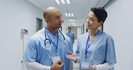podání ruky : Front view of mixed race male doctor and young Caucasian female doctor talking in a hospital corridor and shaking hands. Hospital staff walk past as they talk. 4k Dostupné videozáznamy