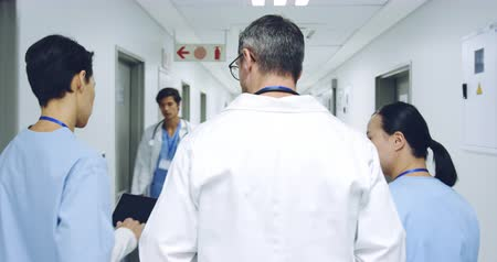 doorway : Waist  up follow shot of three doctors walking down hospital corridor talking. Hospital staff pass by as they walk. 4k Stock Footage