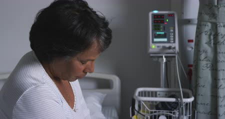apprehensive : Handheld head and shoulders close up of worried senior mixed race woman sitting on the bed in a hospital ward 4k