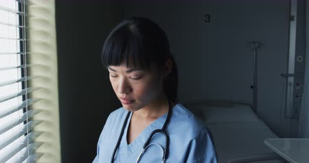 arbustos : Close up of young Asian female doctor working in an empty hospital room, she looks up and smiles to camera 4k Vídeos