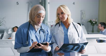 internar : Front view of two female healthcare workers consulting x-rays and talking in a hospital ward. The younger woman is making notes, she is mixed race and wearing a hijab 4k Stock Footage