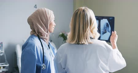 competence : Handheld close up shot of two female doctors consulting x-rays standing in front of the window in a hospital ward.  One is mixed race and wears a hijab, the other is Caucasian and has blonde hair. 4k