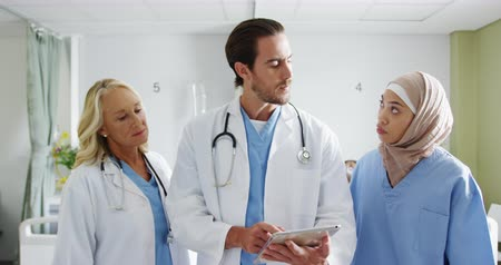 ovmak : Waist up front view of a male and two female multi-ethnic doctors in discussion in a hospital ward consulting a tablet computer 4k Stok Video