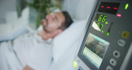 hastane : Close up of hospital equipment monitoring a male patient lying in bed in the background. Focus on equipment in foreground. 4k