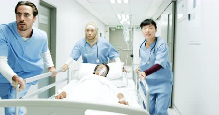 way out : Reverse tracking shot of a diverse team of young healthcare workers ugently pushing a hospital bed down a corridor to rescue a patient, and waving people out of the way. 4k