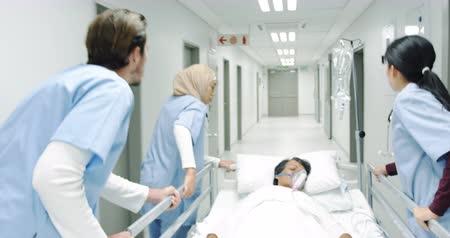 competence : Follow shot of a diverse team of healthcare workers urgently pushing a hospital bed down a corridor to rescue a patient 4k Stock Footage