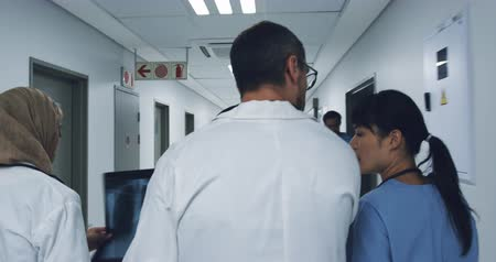 緊急性 : Follow shot of multi-ethnic group of three doctors walking in a hospital corridor talking 4k