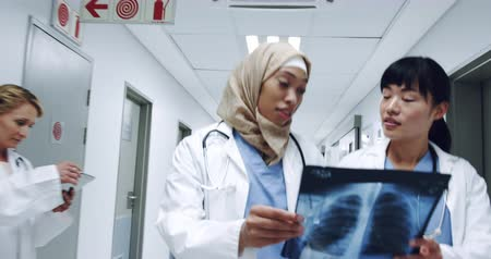 competence : Close up reverse tracking shot of two diverse young female doctors in discussion holding an x-ray as they walk in a hospital corridor 4k