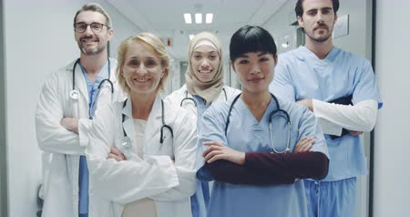 médicos : Close up tilt shot of a multi-ethnic group of doctors standing in a hospital corridor smiling and crossing their arms 4k