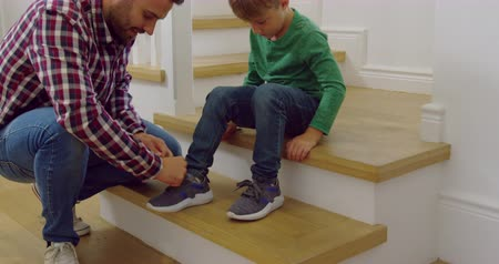 невинность : Side view of Caucasian father tying his sons shoelaces in a comfortable home. They are sitting on stairs 4k Стоковые видеозаписи