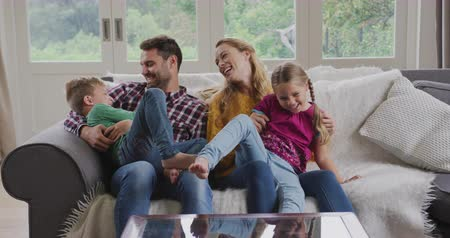 ev gibi : Front view of Caucasian family having fun in a comfortable home. They are sitting on the sofa 4k Stok Video