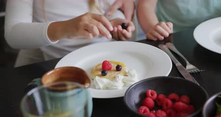 garnishing : Close-up of Caucasian family garnishing food at dining table in a comfortable home. They are putting cream and blueberry on pancake 4k