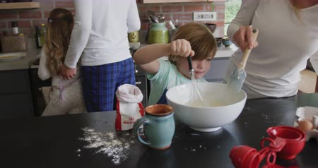 utensílios : Front view of Caucasian mother and son preparing cookie on worktop in kitchen at home. They are stirring flour 4k Vídeos