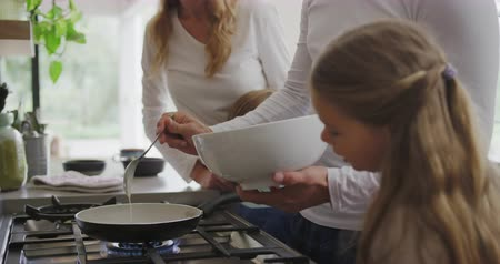 koekenpan : Side view of Caucasian family preparing food in kitchen at home. Father pouring ingredient in pan 4k Stockvideo