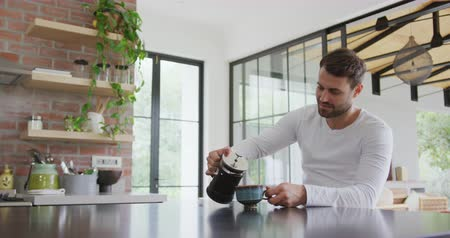 coffee press : Front view of Caucasian man pouring coffee in coffee cup at dining table in a comfortable home. He holding french press 4k