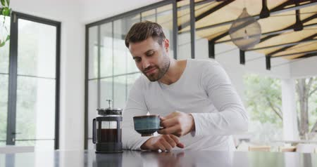fele olyan hosszú : Front view of Caucasian man drinking coffee at dining table in a comfortable home. He is looking at coffee cup 4k Stock mozgókép