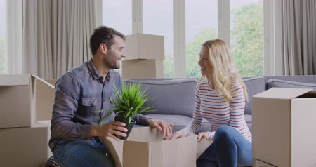 в помещении : Front view of Caucasian couple unpacking cardboard box in new home. They are smiling and talking 4k