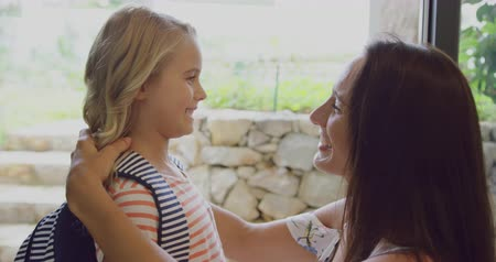 ajoelhado : Close-up of Caucasian daughter embracing her mother before leaving school at door in home. They are smiling and talking 4k Stock Footage
