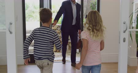 domy : Front view of Caucasian father embracing his two children as he enters the house. They are smiling and happy 4k