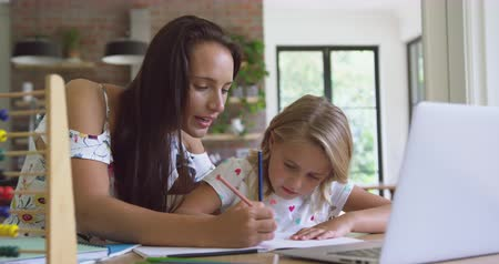 mindennapi : Front view of Caucasian mother helping her daughter with homework in a comfortable home. They are writing on notebook 4k