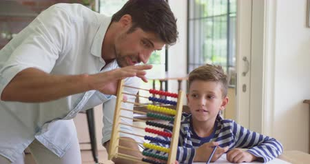 aritmética : Front view of Caucasian father teaching his son mathematics at table in a comfortable home. He is using abacus 4k