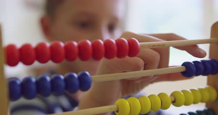 aritmética : Close-up of Caucasian boy learning mathematics with abacus in a comfortable home 4k Stock Footage