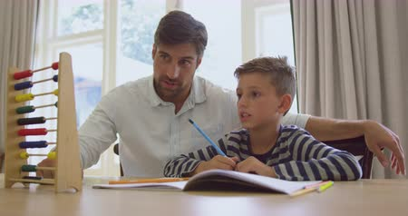 aritmética : Front view of Caucasian father teaching his son mathematics with abacus in a comfortable home. They are sitting at table 4k