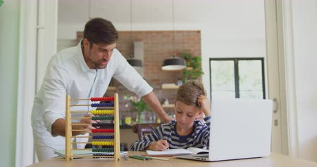 abacus : Front view of Caucasian father helping his son in homework at home. He is interacting with him 4k