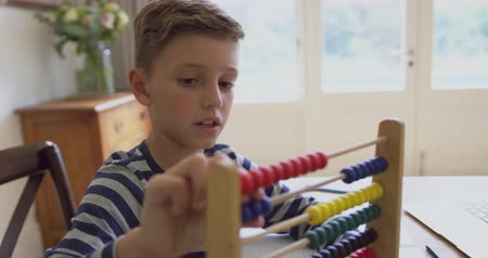 zaměřen : Close-up of Caucasian boy learning mathematics on abacus at table in a comfortable home. He is playing with abacus 4k