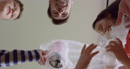 mülkiyet : Upward view of Caucasian family opening cardboard box at new home. They are having fun 4k Stok Video