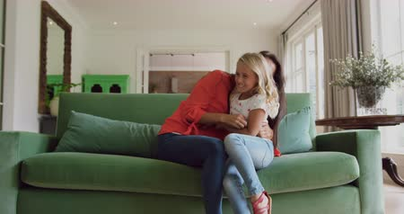 anne : Front view of Caucasian mother and daughter playing together on sofa at home. They are smiling and having fun 4k Stok Video
